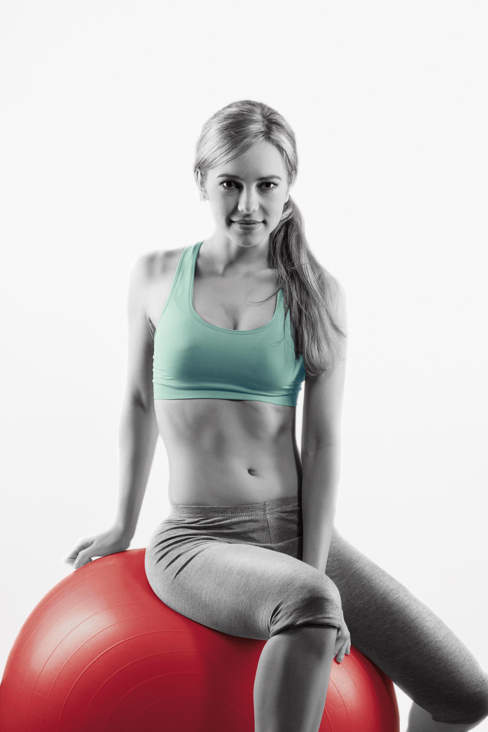 lächelnde junge sportlerin sitzt auf einem fitness ball